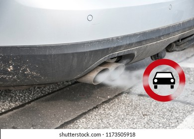 Double exhaust from a car with smoke and the traffic sign for driving ban, in german Fahrverbot for diesel motor vehicles in low emission zones of some cities in Germany, selected focus