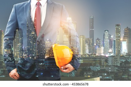 Double exporsure,Copy space for inscription engineer yellow helmet for workers security on the background building and city scape