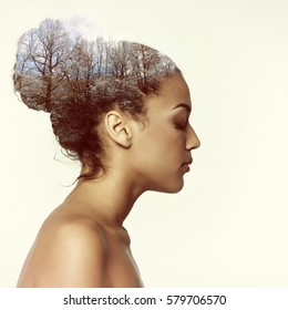 Double exposure beauty portrait of young mulatto woman in profile and mountain winter forest, toned. Dreaming girl. Meditation, spirituality psychological health concept