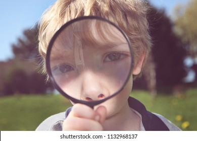 Double exposure of a boy spying through a magnifying glass reflecting a house