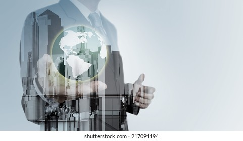 Double exposure of business engineer holding the earth and abstract city as concept