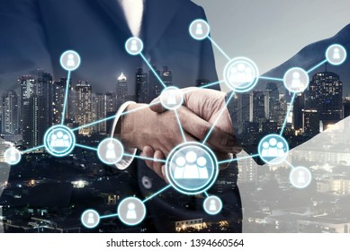 Double exposure of business handshake for successful of investment deal with  organization system and city night background, teamwork and partnership concept.