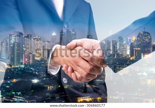 Double exposure of business handshake for successful of investment deal and city night background, teamwork and partnership concept.