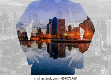 Double exposure of business man Back, looking ahead and night cityscape as vision of leader concept.Young men new business success of asia idea creative leader