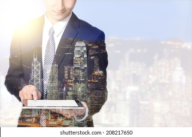 double exposure business man and city - business man using digital tablet with city night skyline, asia, china, hong kong