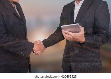 Double exposure of Business man handshake  and hold tablet
