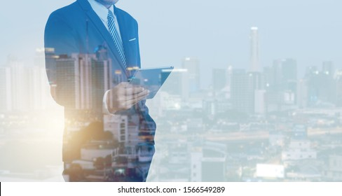 Double exposure of business man holding smartphone Searching for information and city night background.technology for business concept.