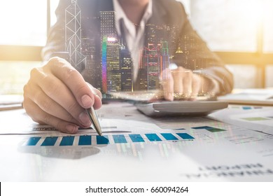 double exposure business man pointing his ideas Data and writing business plan at workplace,man holding pens and making notes trading graph of stock market and using calculator