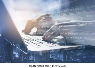Double exposure business man working on laptop computer and the city. Software developer, programmer coding internet mobile app, modern technology, smart business, internet of things IoT concept.