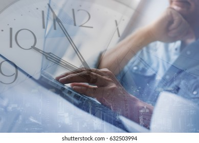 Double exposure of business man working on laptop computer and wall clock and cityscape. Freelancer try to finish  his work on time