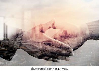 Double exposure of Business partnership meeting concept.photo businessman handshake. Successful businessmen handshaking after perfect deal.close up,London architecture city
