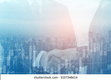 Double exposure of Business people handshaking after successful negotiation and modern buildings in city.business and technology concept.