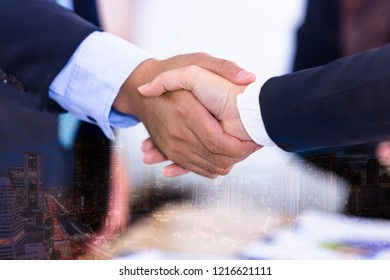 Double exposure business people man and woman shake hand in meeting on city night background