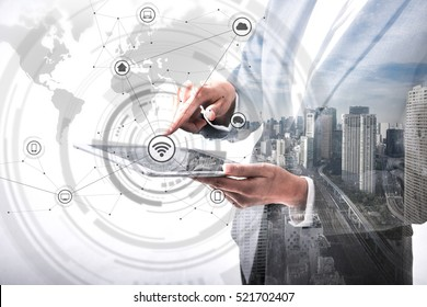 double exposure of business person holding tablet PC and modern cityscape, worldwide marketing information concept