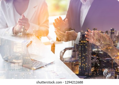 Double exposure of businessman and business women clap their hands to congratulate the signing of an agreement or contract between their companies and city night background. concept of success.