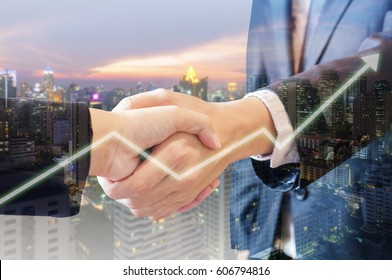 Double exposure of businessman and businesswoman handshake make graph growth with city of business in blue tone background