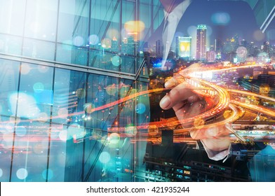 Double Exposure of Businessman draw Something with City Traffic Scene at Night and Glass decorated Building