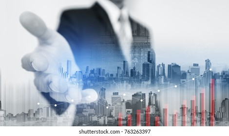 Double exposure Businessman extending hand with buildings in the city and raising graph