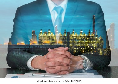 Double exposure of businessman fingers crossed and sit down, Electric generating factory industry at night as energy, meeting, commitment and business concept.