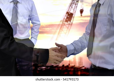 Double exposure of Businessman groups hand shake for business  success concept and construction background . Management construction concept .