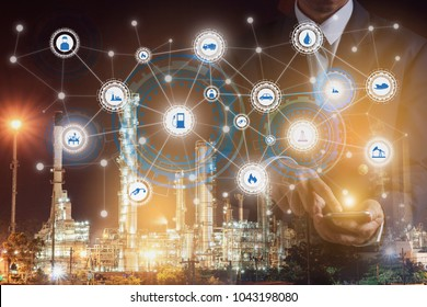 Double exposure of businessman hand hold smartphone working with oil refinery industry plant and industry icons. Factory in the night as communication of energy. Smart technology 4.0 and communication