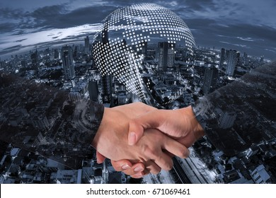 Double exposure of a businessman handshake on Earth map circle of world global network cartography globalization with blue tone aerial view of modern buildings and  condominium in the city downtown.