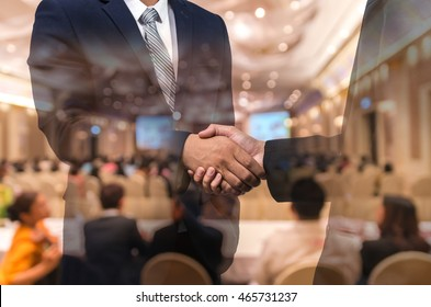 Double exposure of businessman handshake over the Abstract blurred photo of conference hall or seminar room with attendee background, business agreement concept