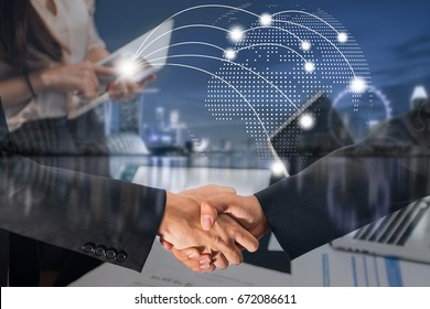 Double Exposure of a businessman handshake with world map point global network connection globalization on cityscape in business district blue tone aerial view background, worldwide business concept.