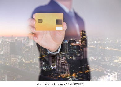 Double exposure of businessman hold, show bebit or credit card and cityscape in the twilight as business, investment, payment and advertising concept.