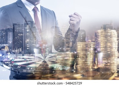 Double exposure of Businessman holding arrow on dart board with step of coins and blur city night background, achieve target to victory concept
