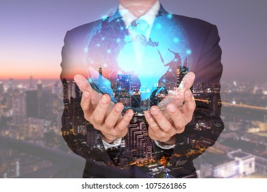 Double exposure of businessman holding the glowing polygonal hologram digital globe and cityscape in the night or twilight as business, innovation, intelligent and idea concept
