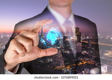 Double exposure of businessman holding the glowing polygonal hologram digital globe and cityscape in the twilight or night as business, innovation, intelligent, idea and saving world concept.