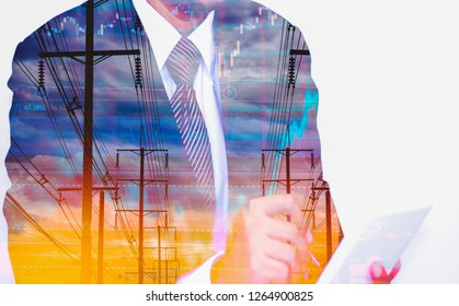 Double exposure Businessman holds tablet, with electric pole, and sky stock graph background, concept of volatility of stocks and energy businesses in global market.