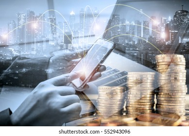 Double exposure of businessman investor using smart phone at office with city night and step of coins background, ,on-line banking and investment concept
