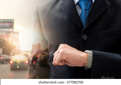 Double exposure businessman looking his watch to check time and bad traffic. Look like his is in a hurry in rush hour and traffic is so bad.