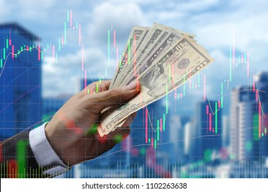 Double exposure of businessman Pay the US dollar with cityscape and stock market or financial graph for financial investment concept.