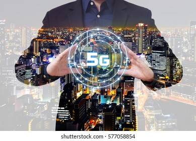 Double exposure businessman show 5G symbol between two hands with city overlay background