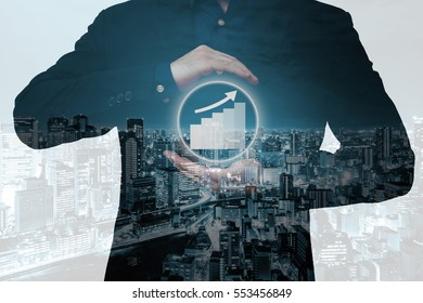 Double exposure of businessman showing growth graph with city overlay