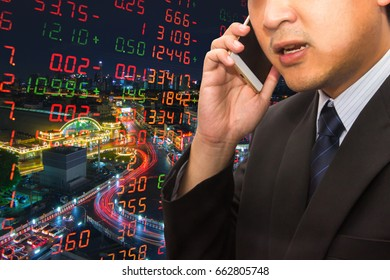 Double exposure a Businessman in suit using smart phone to call with stocks board and Bangkok night city background. Securities investor are busy concept.