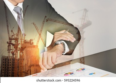 Double exposure of businessman take time in appointments, construction crane, building and sunset in the evening as business, vision of leader and industry concept