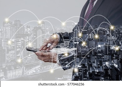Double exposure businessman touching on smartphone with city overlay and connected line background