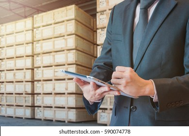 Double exposure of businessman touching tablet analyze and checking stock at transportation port with blurred cargo warehouse background, international transportation trading business concept