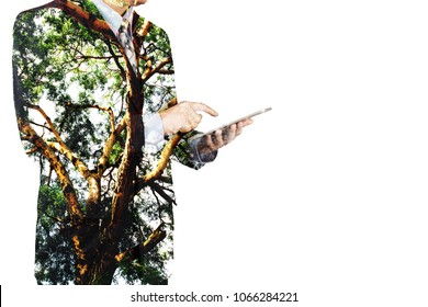 Double Exposure of Businessman use Digital Wireless Tablet with Tree and Branch as Business CSR or Technology with Nature Conservation and Freedom Think Concept.