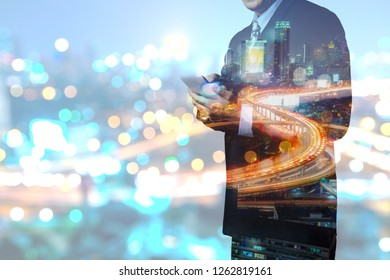 Double Exposure, Businessman use Mobile Smartphone device with Night City Building and Clear Street Light Trail and Blur Bokeh as 5G Technology on Mobilephone Communication.