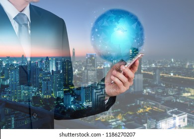 Double exposure of businessman use smartphone, blue world, communication 5G node networking telephone cellsite and cityscape urban in the night or twilight as business, technology and telecom concept