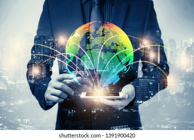 double exposure of businessman using cellphone or smart phone and globe simulation with blur city night, network technology connection concept