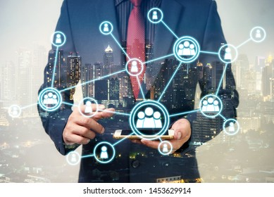 double exposure of businessman using cellphone or smart phone with organization system and city night background, network technology connection concept