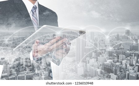 Double exposure businessman using digital tablet, and cityscape. Business network, blockchain technology and internet connection