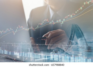Double exposure of businessman using the laptop computer on monitor of stock market financial graph with cityscape building background, Business trading strategy analysis concept