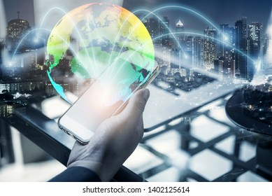 Double exposure of businessman using smart phone show globe simulation at office with city night background, digital network connection concept